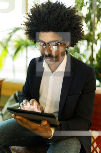Businessman sitting on bench using tablet