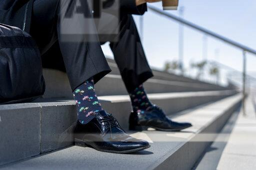 Close-upof businessman sitting on stairs wearing patterned socks