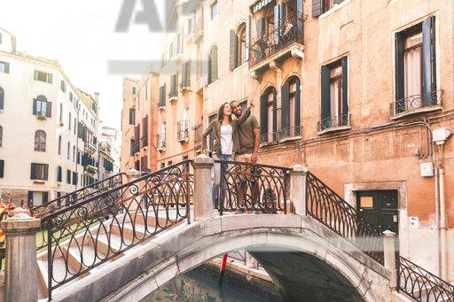 Italy, Venice, young couple standing on a small bridge exploring the city
