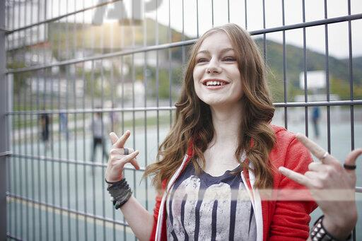 Portrait of a happy teenage girl gesturing at a fence at a sports field