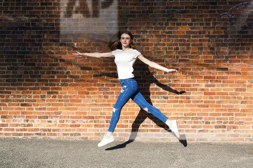 Agile young woman jumping in front of brick wall