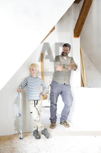 Portrait of smiling father and son working on loft conversion