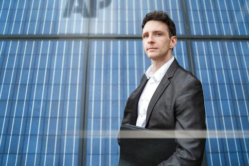 Businessman holding folder standing in front of solar panels