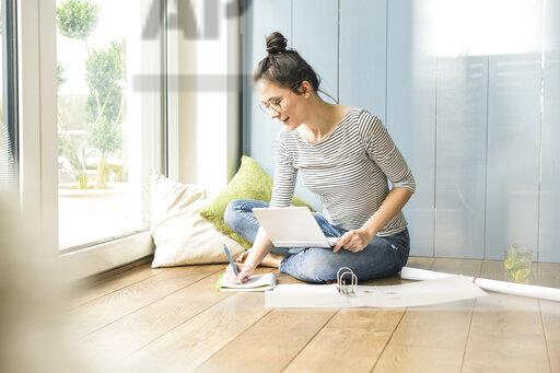 Woman sitting at the window at home taking notes