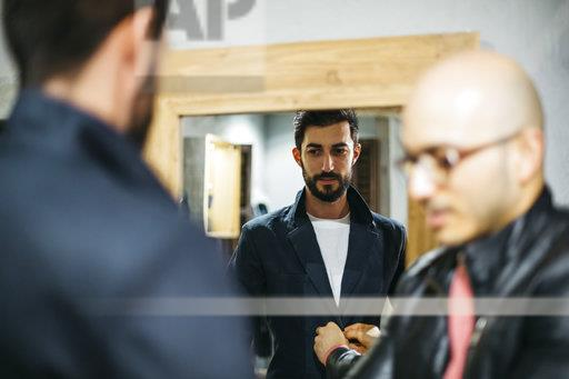 Man with client wearing new stylish suit in front of mirror