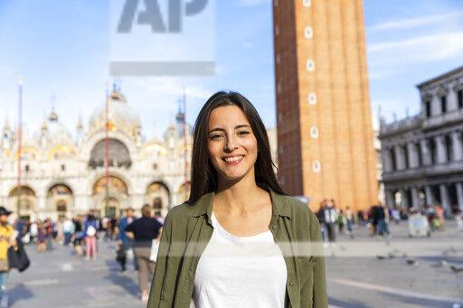 Italy, Venice, portrait of smiling young woman on St Mark's Square