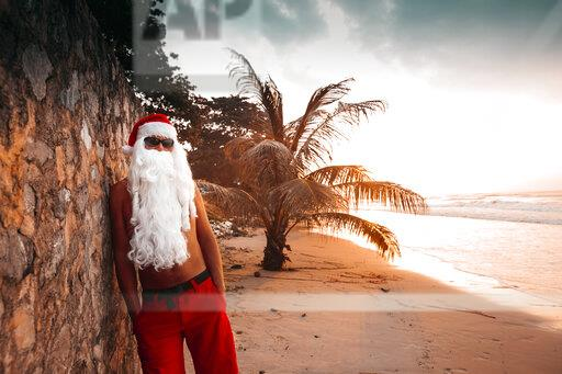 Thailand, man dressed up as Santa Claus leaning against wall on the beach at sunset