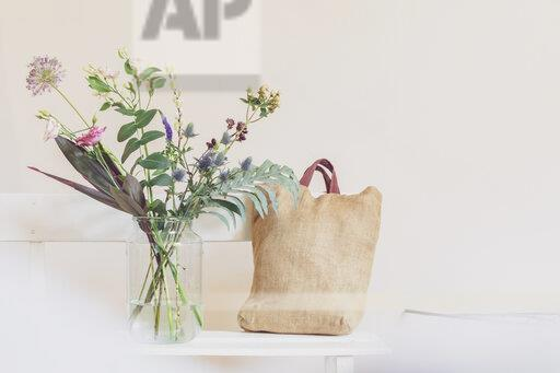 Flower vase and open calendar on white bench, linen shopping bag