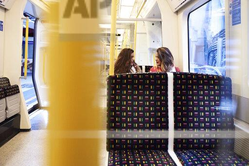 UK, London, two women talking in underground train