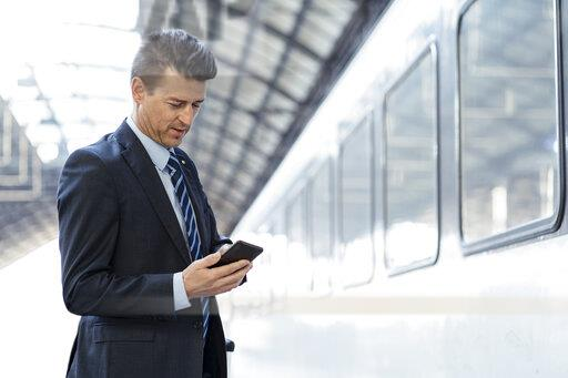 Businessman using cell phone on station platform