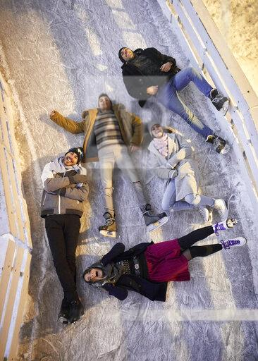 Happy friends lying on an ice rink at night