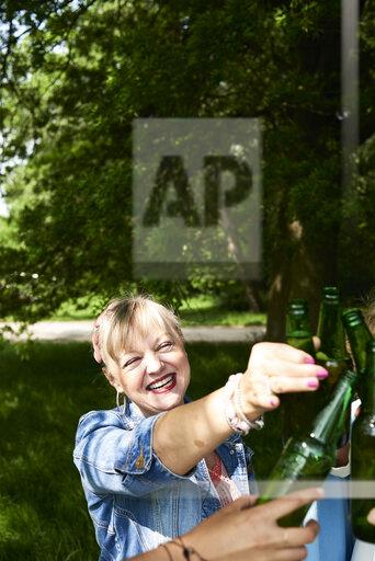 Portrait of happy woman clinking beer bottle with friends in park