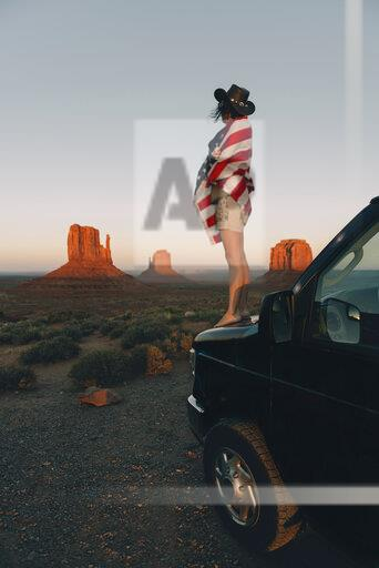 USA, Utah, Monument Valley, Woman with United States of America flag enjoying the sunset in Monument Valley