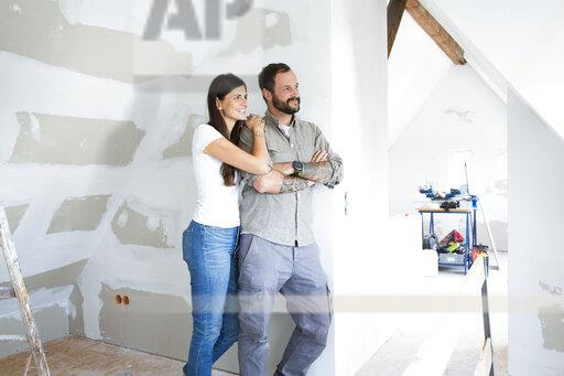 Smiling couple in attic to be renovated looking out of window