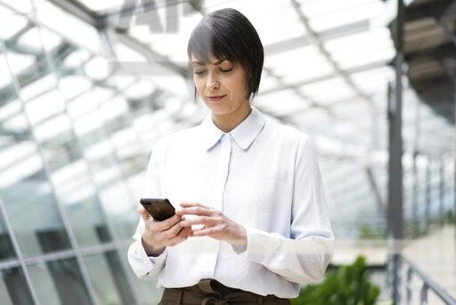 Businesswoman using smartphone i atrium of office building