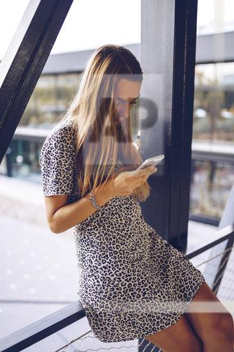 Attractive young woman in leopard print dress checking cell phone