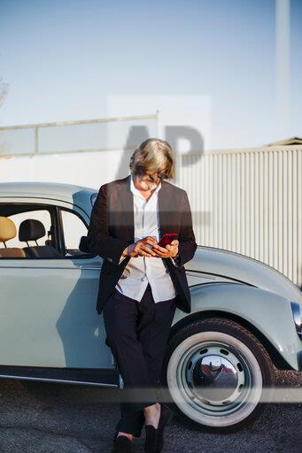 Senior man standing in front of vintage car using mobile phone