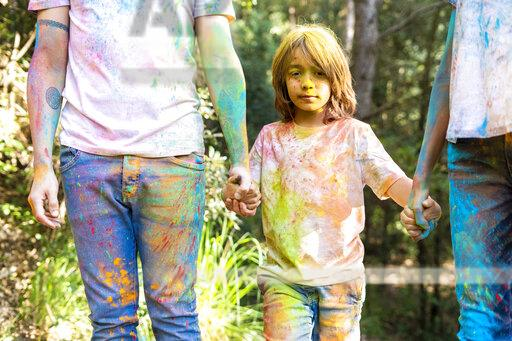 Family in the forest, full of colorful powder paing, after celebrating Holi, Festival of colors