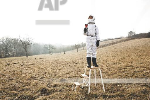 Boy wearing white space suit with flashlight on step