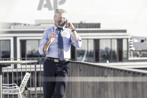 Smiling mature businessman on cell phone on roof terrace