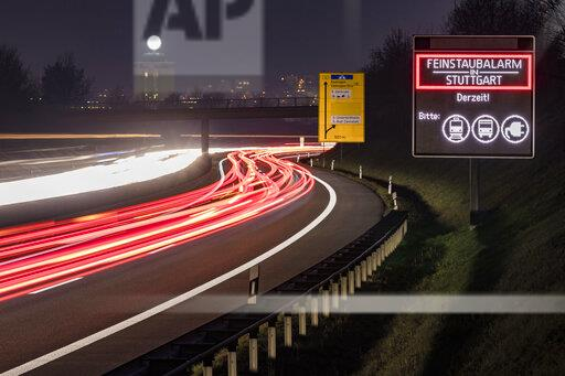 Germany, Stuttgart, Warning sign for particulate pollution alert and traffic at night
