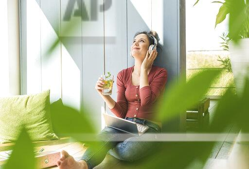 Smiling woman with headphones and laptop sitting at the window at home