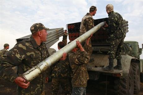 Ukrainian soldiers load a Grad missile during fighting with pro-Russian separatists close to Luhansk, eastern Ukraine, Monday, Aug. 18, 2014. Dozens of civilians were killed Monday when separatist rebels shelled a convoy of refugees trying to flee war-torn eastern Ukraine, a top Ukrainian official said. A top rebel chief said no such attack had occurred. (AP Photo/Petro Zadorozhnyy)