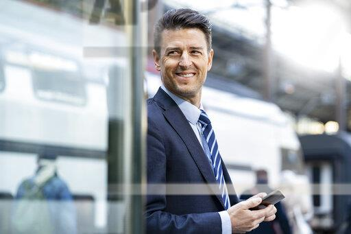 Smiling businessman with cell phone at train station