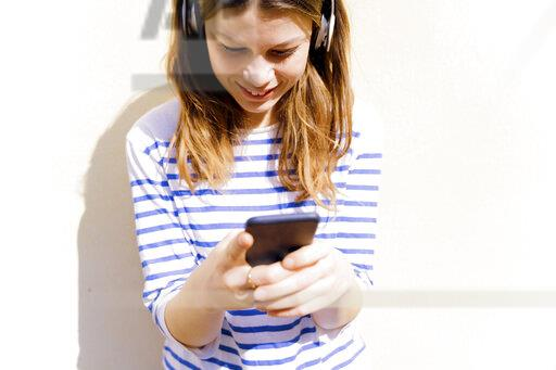 Young woman sith geadphones using smartphone