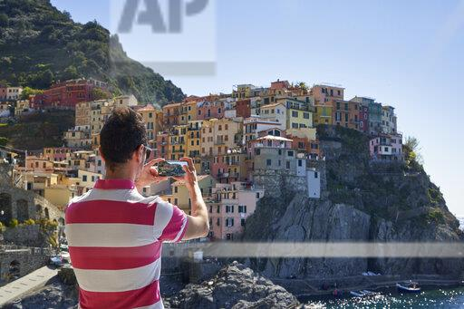 Italy, Liguria, La Spezia, Cinque Terre National Park, man using smartphone, photographing Manarola