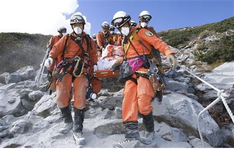 In this Sunday, Sept. 28, 2014 photo released by Tokyo Fire Department, firefighters carry a hiker trapped in the summit area of Mount Ontake during Saturday's initial eruption during rescue operations in central Japan. A dozen more bodies were found Wednesday, Oct. 1 near the ash-covered summit of the Japanese volcano as searches resumed amid concern of toxic gasses and another eruption. (AP Photo/Tokyo Fire Department)