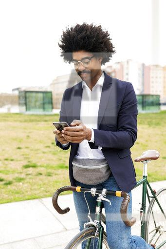 Spain, Barcelona, businessman on bicycle using cell phone in the city