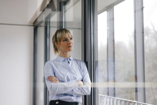 Successful businesswoman in conference room, with arms crossed