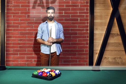 Portrait of serious man at billiard table