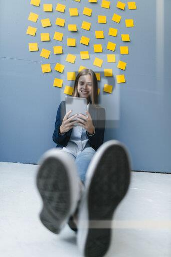 Young businesswoman sitting under data cloud, using digital tablet
