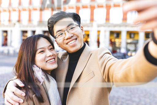 Spain, Madrid, happy young couple taking a selfie in the city