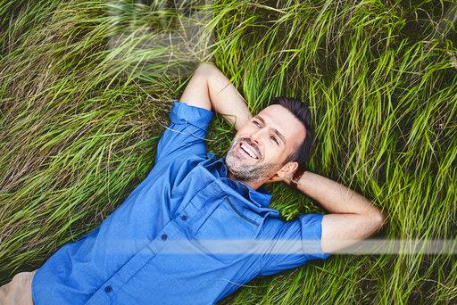 Relaxed happy man lying in grass