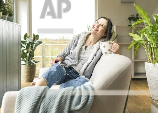 Happy woman with a mug and tablet sitting on the couch at home