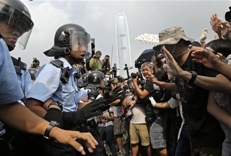 Riot police try to hold back protesters as an ambulance tries to leave the compound of the chief executive office in Hong Kong, Friday, Oct. 3, 2014. Hong Kong protesters on Friday welcomed an overnight offer by the territory's leader of talks to defuse the crisis over demonstrations seeking democratic reforms, though they continued to demand he resign and maintained barricades around government headquarters, frustrating staff going to work.