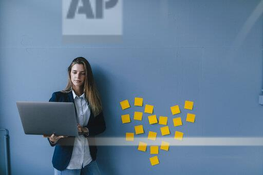 Young businesswoman using laptop with heart shape of sticky notes on the wall