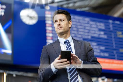 Businessman with cell phone at the station