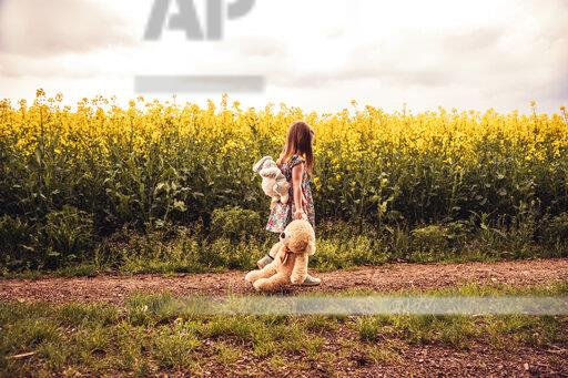 Girl walking alone with teddy and backpack on a field way