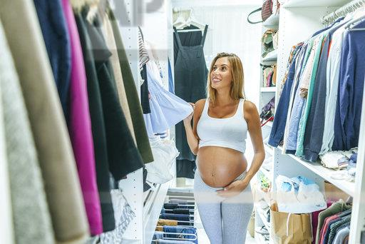 Pregnant woman looking at clothes in a dressing room