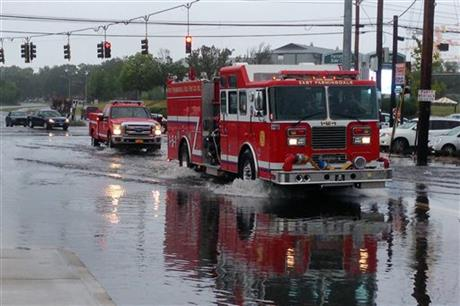 Firefighters cross a flooded intersection on Route 110 in Farmingdale, N.Y., on New York's Long Island, Wednesday, Aug. 13, 2014. Stranded Long Island drivers have been rescued after a storm slammed Islip, N.Y., with over 12 inches of rain — an entire summer's worth. (AP Photo/Frank Eltman)