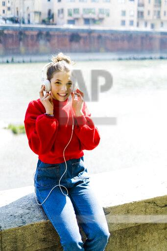 Young woman in Verona, riverside, listening music