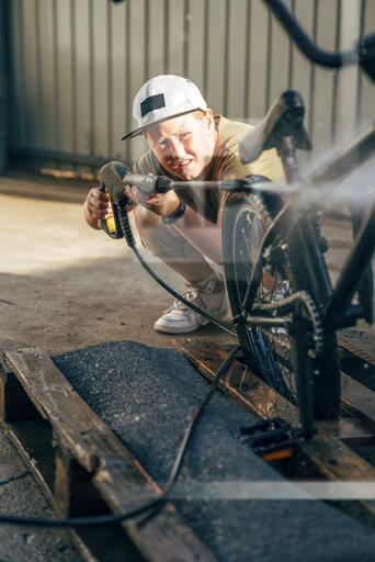 Boy washing bmx bike with pressure washer on yard