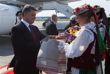 Ukrainian President Petro Poroshenko gets traditional salt and bread upon arrival in Minsk, Belarus on Tuesday, Aug. 26, 2014. Poroshenko arrived in Minsk on Tuesday for discussions with Russia and Ukraine with a view to creating a new political impulse towards finding a political, sustainable solution to the situation in Ukraine. (AP Photo/ Dmitry Brushko)