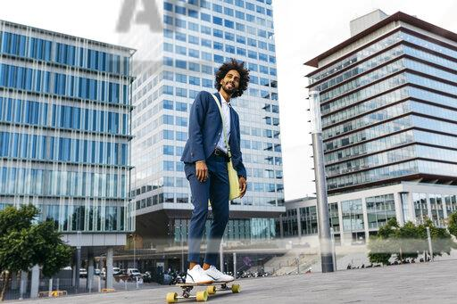 Spain, Barcelona, young businessman riding skateboard in the city