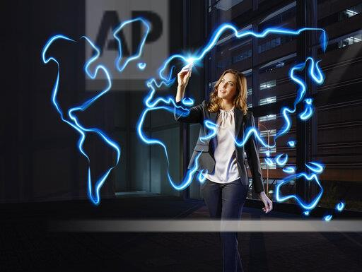 Businesswoman painting a worldmap with light, pointing on Europe