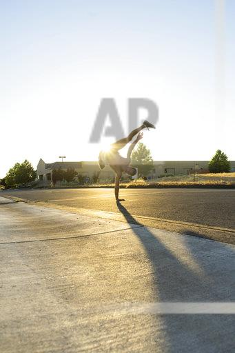 Acrobat practicing one-armed handstand on a road at sunset